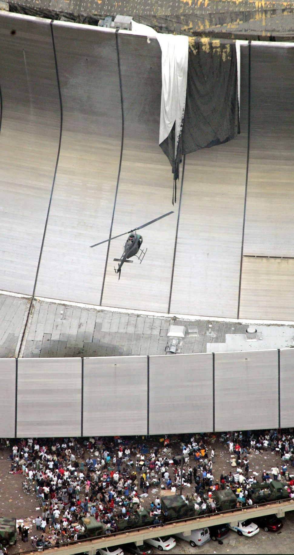 A helicopter flies over residents waiting to be evacuated from the Louisiana Superdome in New Orleans, Sept. 1, 2005.