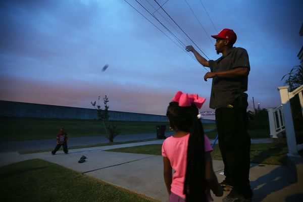 Troy Richard plays football with his kids outside their home in front of the rebuilt Industrial Canal levee wall in the Lower