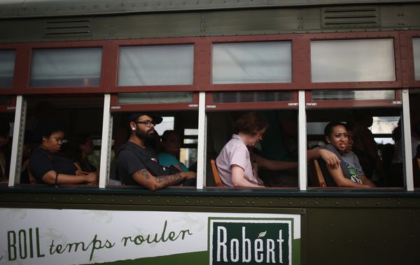 People ride an original heritage streetcar on the St. Charles Avenue line on May 14, 2015 in New Orleans, Louisiana. While so