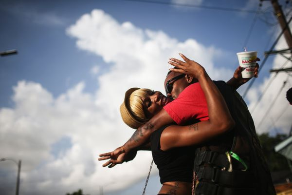 Revelers embrace at the conclusion of the Zulu Social Aid and Pleasure Club 'second line' parade on May 17, 2015 in New Orlea