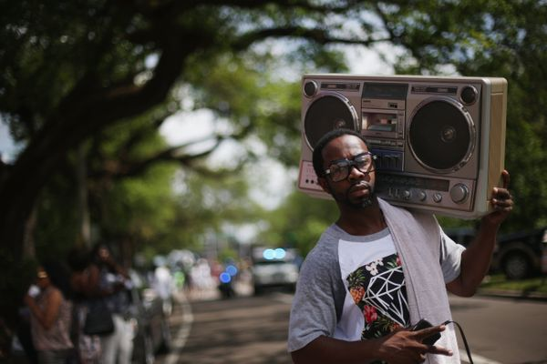 A man carries a boom box during the Original Big 7 Social Aid and Pleasure Club 'second line' parade on May 10, 2015 in New O
