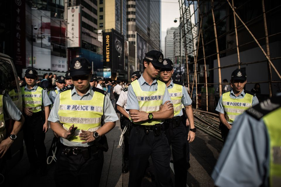 Policemen walk away from a scene where anti demonstrators confronted pro-democracy demonstrators in an occupied area of Hong