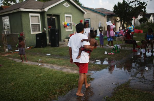 People gather at a birthday party at a repaired house which was flooded during Hurricane Katrina in the Lower Ninth Ward on M