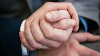 Close-up of a gay couple holding hands during their wedding ceremony