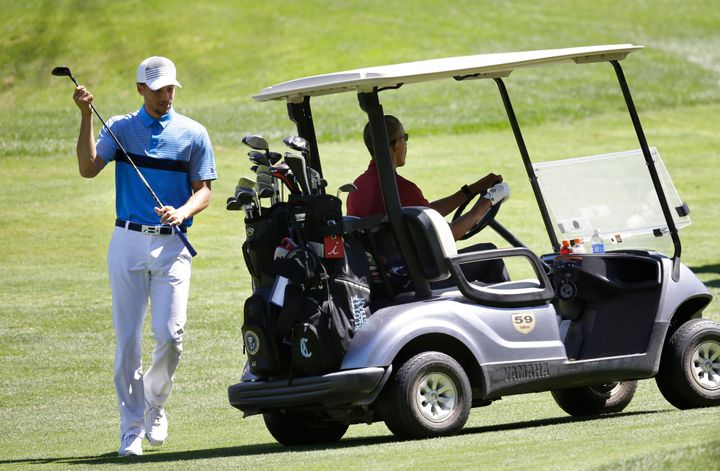 NBA basketball player Stephen Curry, left, returns a club to the cart as President Barack Obama, right, prepares to drive whi