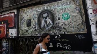 <p>A pedestrian passes a street mural of a banknote resembling a U.S. dollar bill, by graffiti artist N_Grams, in Athens, Greece, Aug. 19. 2015. </p>