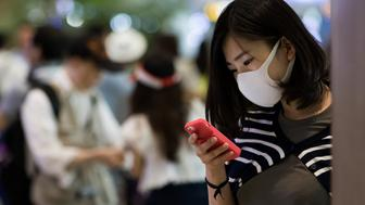 A Japanese tourist wearing a face mask looks her smartphone at Incheon International Airport in Incheon, South Korea, on Monday, June 8, 2015. South Korea reported its sixth death from the Middle East respiratory syndrome (MERS), with the total number of cases rising to 87, including the first teenager to be infected with the virus. Photographer: SeongJoon Cho/Bloomberg via Getty Images