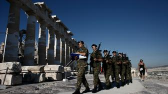 Greek army soldiers perform a ceremonial march past the Parthenon temple before raising the national flag on Acropolis Hill in Athens, Greece, on Wednesday, Aug. 19. 2015. Greece's third bailout cleared one of its last hurdles after the German parliament voted in favor of the aid package of as much as 86 billion euros ($95 billion). Photographer: Kostas Tsironis/Bloomberg via Getty Images