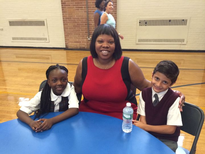 Aleeya Francis, principal of St. Charles Borromeo School in Harlem, sits with students Farida Mintoumba (left) and Essa Nahsh