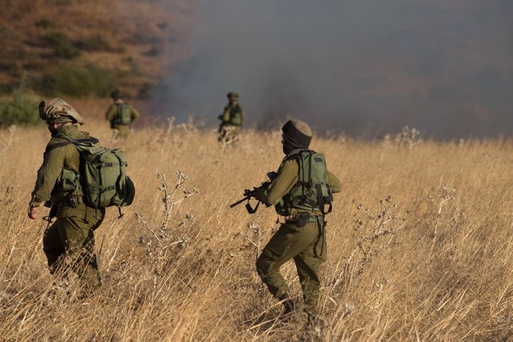 Israeli soldiers inspect a field where rockets fired from Syria landed near Kfar Szold in northern Israel, close to the Golan