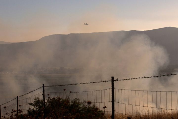 An Israeli firefighters plane flies over a field where rockets fired from Syria landed near Kfar Szold in northern Israel, cl