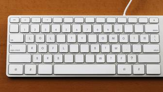 A computer keyboard with its keys rearranged providing convenient access to commonly used internet acronyms and kaomoji.