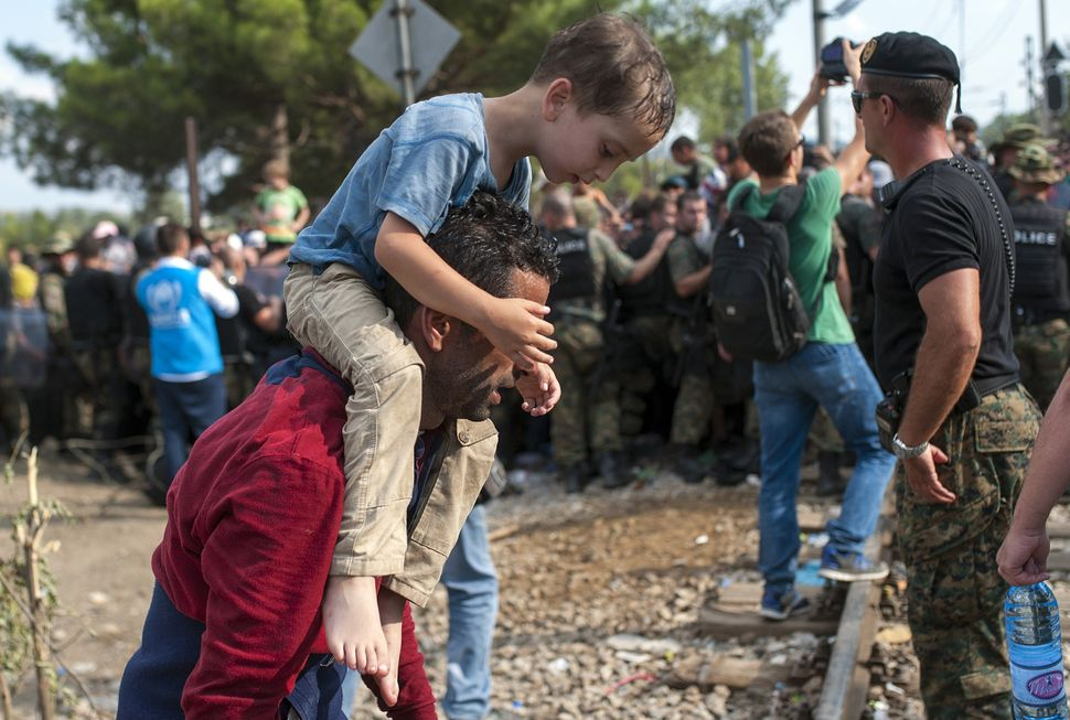 Refugees and migrants are held back by police as they try to cross the Macedonian-Greek border near the town of Gevgelija, Ma