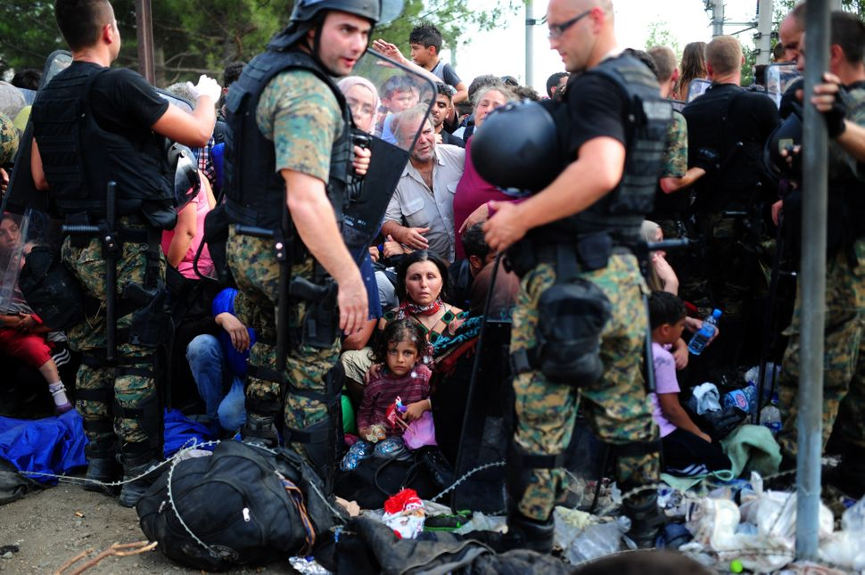 Police block the way as migrants and refugee families try to cross the Macedonian-Greek border near the town of Gevgelija, Ma