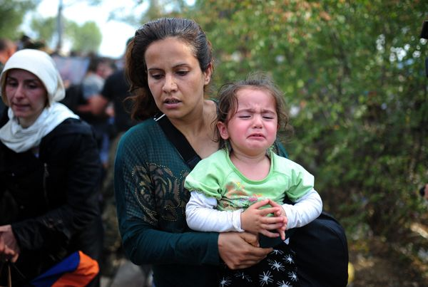 Migrant and refugee families try to cross the Macedonian-Greek border near the town of Gevgelija, Macedonia, on Aug. 21, 2015