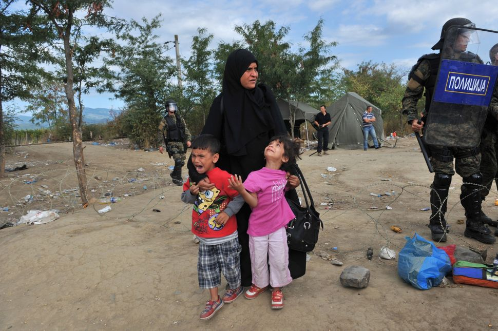 A woman with children waits to pass the Greek-Macedonian border, guarded by Macedonian police near the town of Idomeni, north