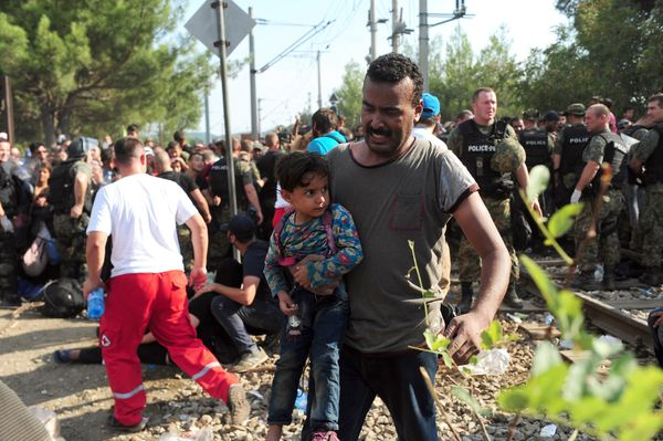 Police are seen as migrant and refugee families try to cross the Macedonian-Greek border near the town of Gevgelija, Macedoni