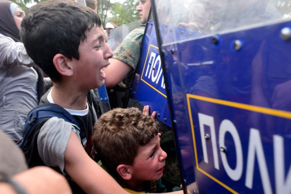 Two boys cry as Macedonian police block a group of migrants trying to cross an illegal crossing point on the border between G