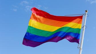 Close-up of a rainbow flag on blue sky.