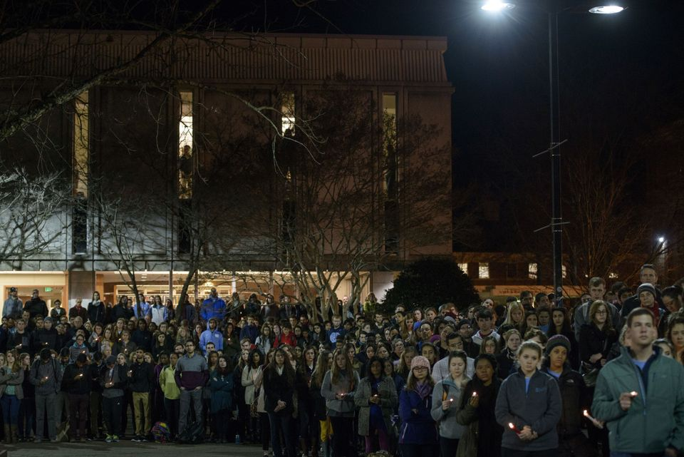 People listen during a vigil at the University of North Carolina following the murders of three Muslim students on February 1