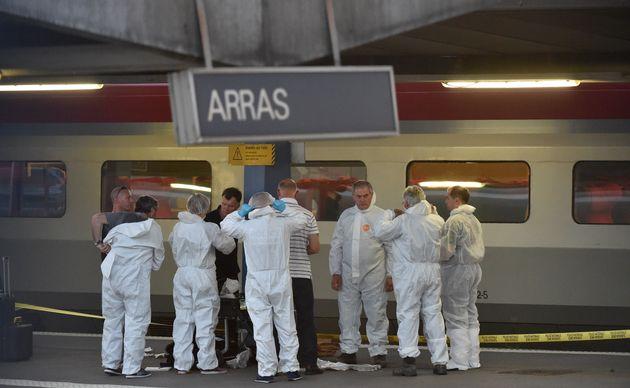 Criminal and forensic investigators stand on a platform at atrain station in Arras, France, on...