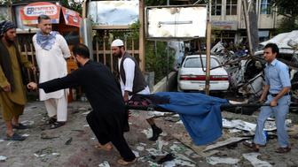 GRAPHIC CONTENT Afghan rescuers carry the body of a woman at the site of a car bomb in Kabul on August 22, 2015. A suicide car bomb apparently targeting a foreign forces convoy killed three people in downtown Kabul on August 22, officials said, underlining the precarious security situation in the Afghan capital following a recent wave of fatal bombings. AFP PHOTO / WAKIL KOHSAR        (Photo credit should read WAKIL KOHSAR/AFP/Getty Images)