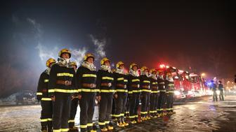 HARBIN, CHINA - JANUARY 08:  (CHINA OUT) Firemen stand to salute firefighters's who died in Harbin's fire at Tianhe Funeral Parlour on January 8, 2015 in Harbin, Heilongjiang province of China. Five firemen were killed and 17 were injured during a fire in Harbin on January 2. (Photo by ChinaFotoPress/ChinaFotoPress via Getty Images)