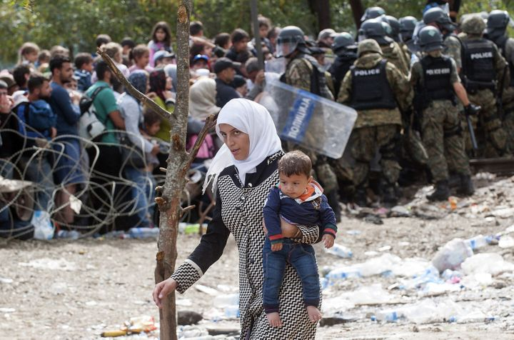 A woman carries a baby during a clash between Macedonian police forces and people trying to cross the border betwee