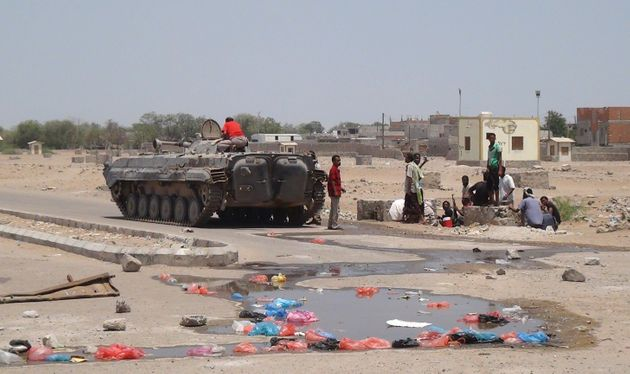 Yemenis sit near a tank used by members of the southern separatist movement parked in a deserted street...