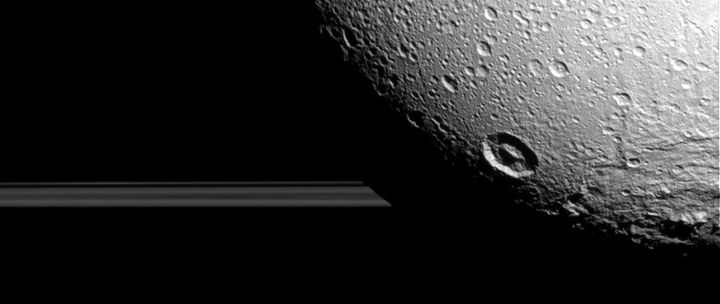 One of the newlyreleased images of Dione, a moon of Saturn, showing the rings of Saturn behind it. Thenew images