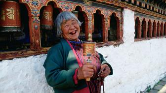 BHUTAN - FEBRUARY 11:  An old woman with prayer wheels laughing at the Kyichu Buddhist Temple in Paro, Bhutan.  (Photo by Tim Graham/Getty Images)