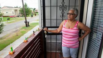 NEW ORLEANS, LA - JULY 22: Mary Picot looks out from the balcony of her home near a levee in the Lower Ninth Ward, on July 22, 2015 in New Orleans, Louisiana. Her original house was destroyed when the levee broke. It's been ten years since hurricane Katrina devastated neighborhoods throughout the city. Her house was built by Brad Pitt's foundation. While many homes have been rebuilt, there are still many empty lots where homes used to stand. (Photo by Melanie Stetson Freeman/The Christian Science Monitor via Getty Images