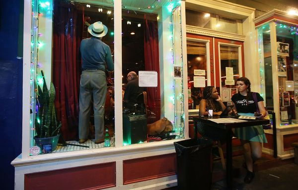 A band member stands performing in a music club on Frenchmen Street, a live music area traditionally known by locals but now
