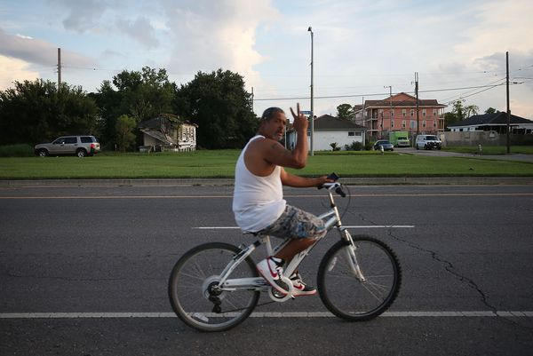 A man waves while bicycling past a destroyed home (TOP L) in the Lower Ninth Ward on August 20, 2015 in New Orleans, Louisian