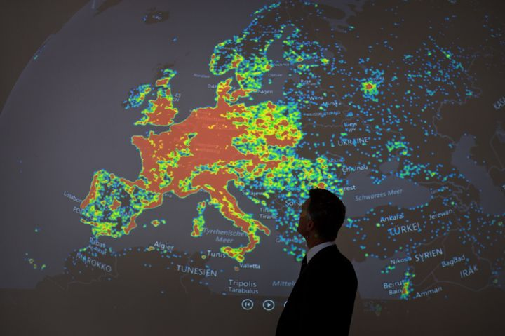 """A man stands in front of a picture displaying activities of a so-called """"botnet"""" in Frankfurt am Main, Germany, on July 31, 2"""