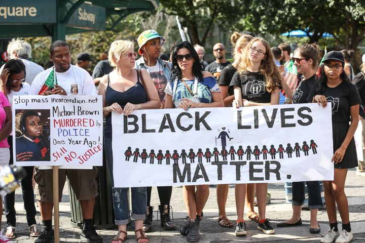 """Protesters march behind a banner of """"Black Lives Matter"""" on August 9 in New York, one year after the death of unarmed black t"""
