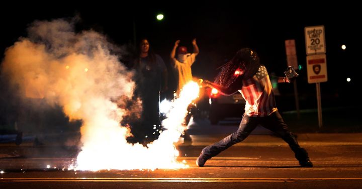 A demonstrator throws back a tear gas container as police try to break up a group of bystanders near West Florissant Avenue o