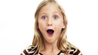 Portrait of smiling girl looking surprised, studio shot