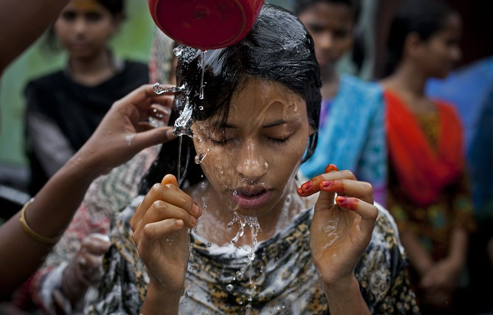15-year-old Nasoin Akhter is bathed on the day of her wedding to a 32-year-old man, Aug. 20, 2015 in Manikganj, Bangladesh.