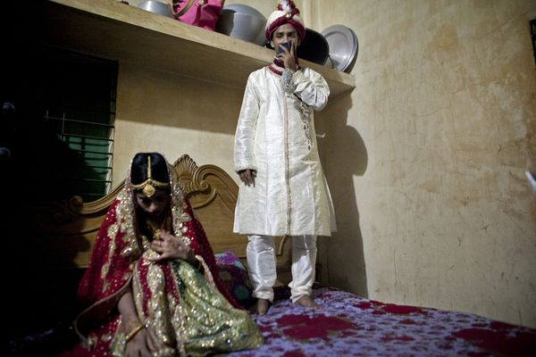 32-year-old Mohammad Hasamur Rahman stands on a bed next to his new bride, 15-year-old Nasoin Akhter, Aug. 20, 2015 in M