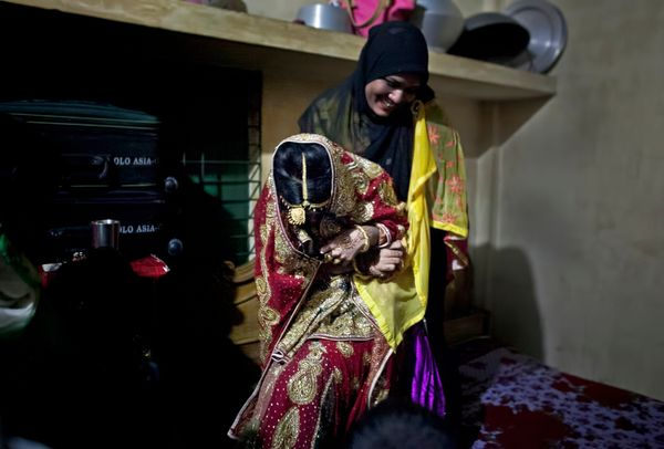 A relative drags 15-year-old Nasoin Akhter onto a bed to pose for photographs on the day of her wedding to a 32-year-old
