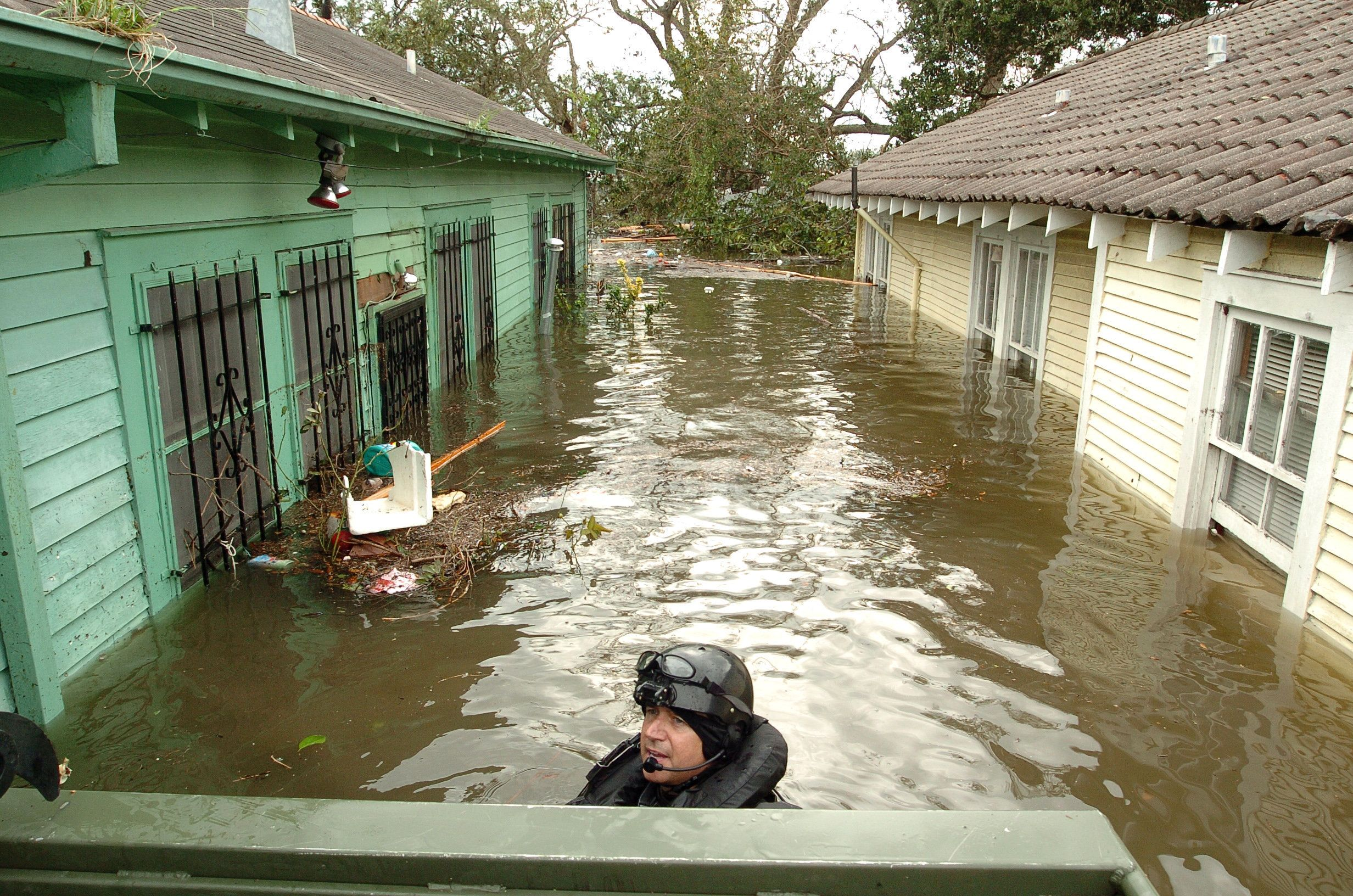 NEW ORLEANS - AUGUST 29: Swat police officer Cris Mandry navigates a rescue boat through a flooded alley looking for survivors in the Lower Ninth Ward in New Orleans, Louisiana on August 29, 2005. Hurricane Katrina slammed Louisiana as a category 4 storm, forcing levies to brake and flooding much of New Orleans. (Photo by Marko Georgiev/Getty Images)