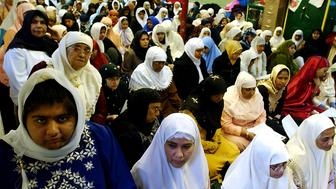 NEW YORK - DECEMBER 6:  Muslim women prepare to pray during the service at the Masjid Al-Abidin mosque December 6, 2002 in the Queens borough of New York City. Eid al-Fitr is the Muslim holiday after the end of the month-long fast of Ramadan.  (Photo by Stephen Chernin/Getty Images)