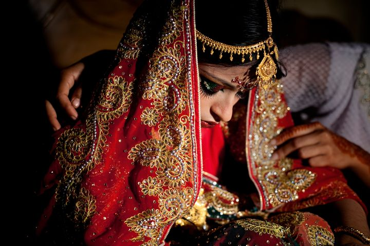 15-year-old Nasoin Akhter is consoled by a friend on the day of her wedding to a 32-year-old man, Aug. 20, 2015 in Manikganj,