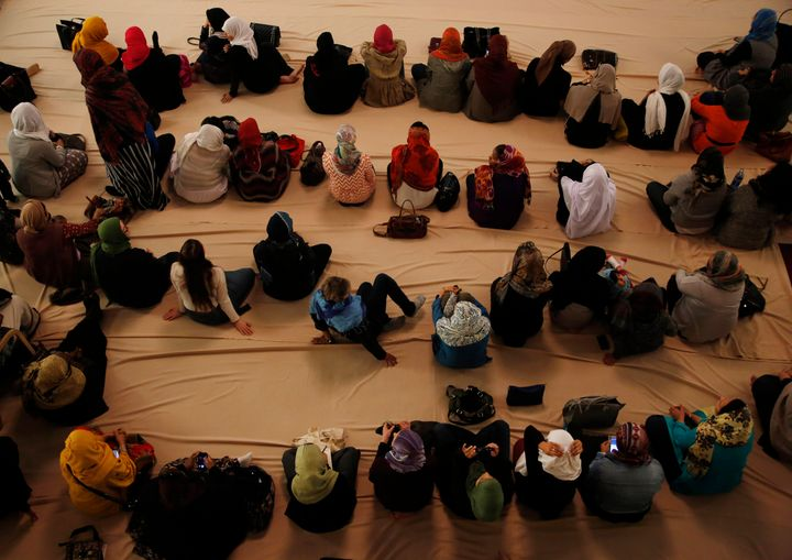 Muslim women prepare to pray during the service at the Masjid Al-Abidin mosque December 6, 2002 in the Queens borough of New