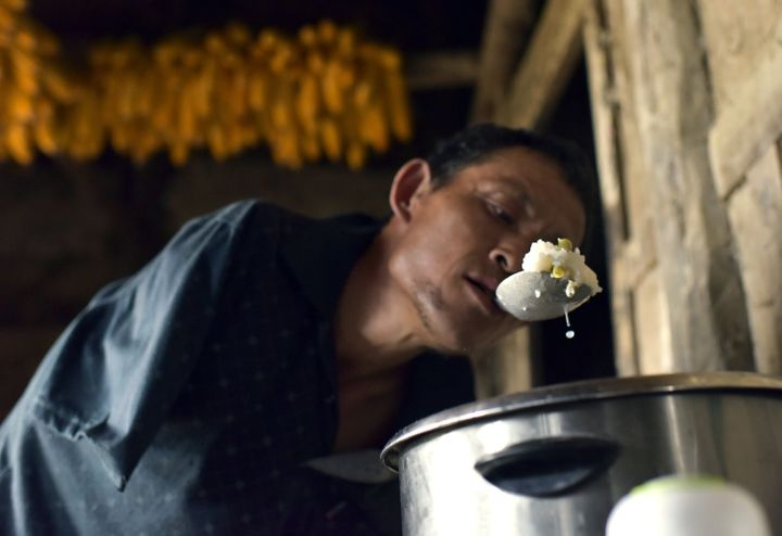 Chen Xingyin holds a spoon in the mouth to fill a bowl with rice.