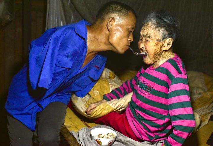 <p>Chen Xingyin holds a spoon in his mouth to feed his mother.</p>