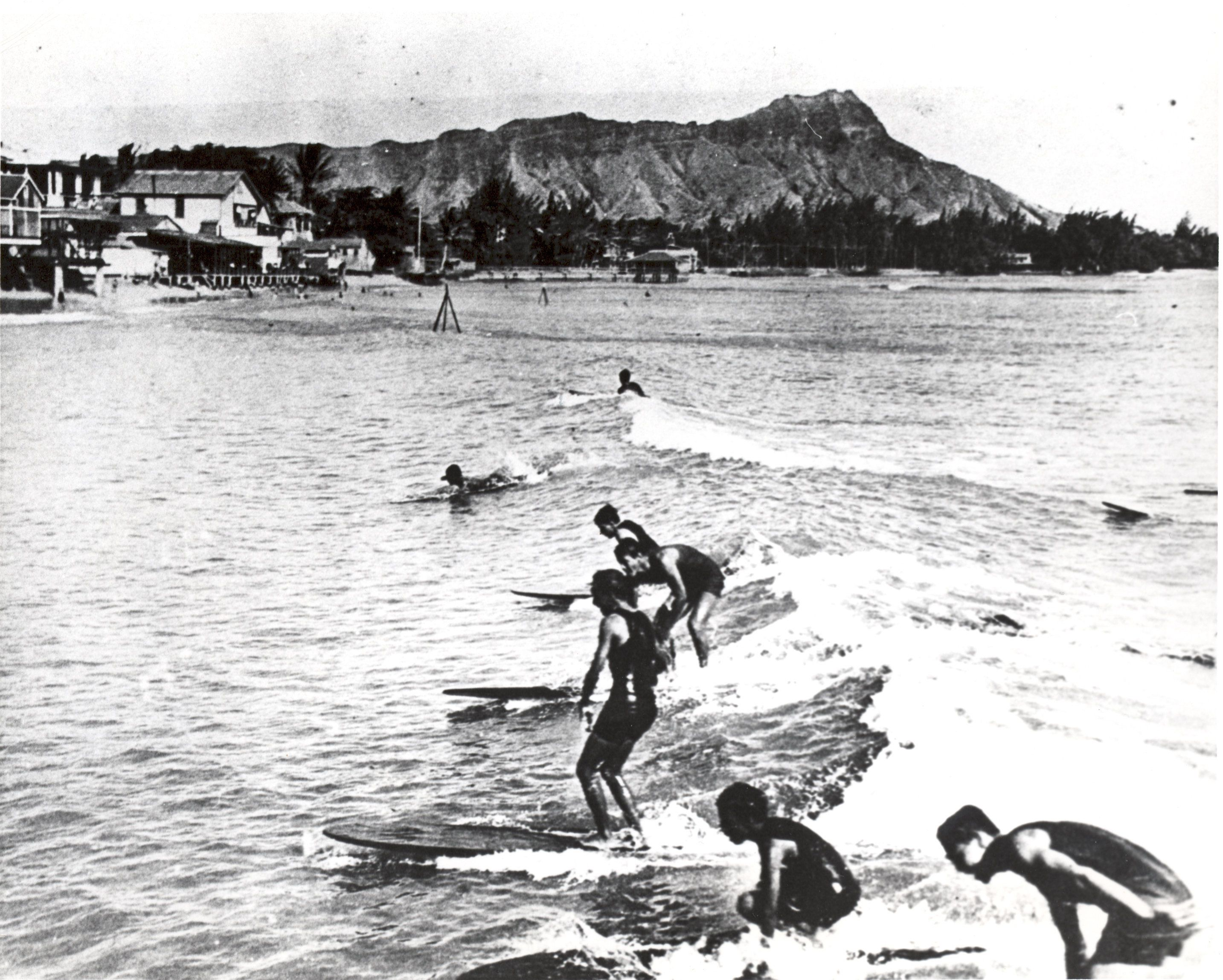 Surfers ride the waves at one of Waikiki's famed surf breaks in the early 1900s.