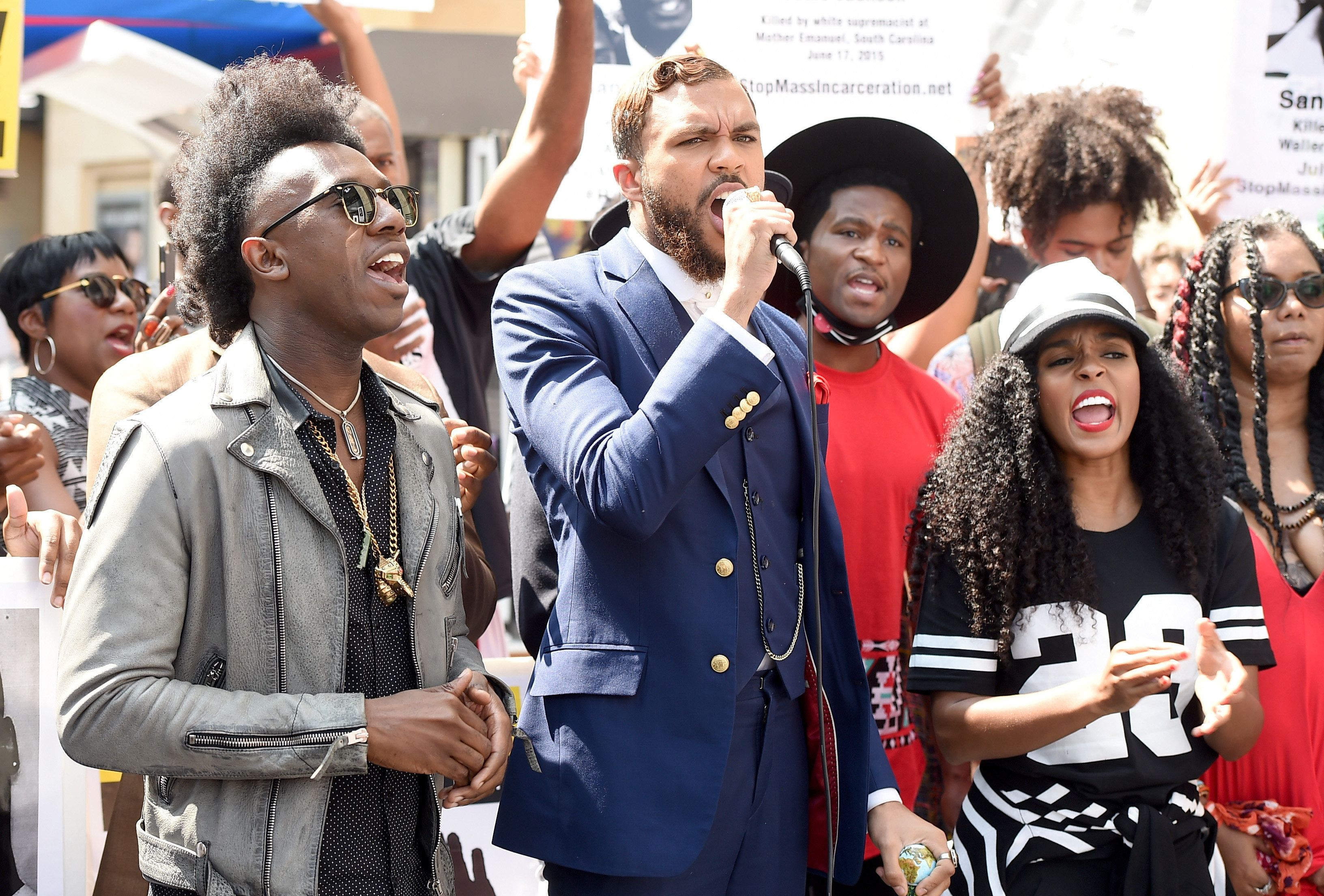 LOS ANGELES, CA - AUGUST 21:  Singers Jidenna (in bkue suit) and Janelle Monae perform and protest in coordination with Stop Mass Incarceration Network at Hollywood and Highland on August 21, 2015 in Los Angeles, California.  (Photo by Kevin Winter/Getty Images)