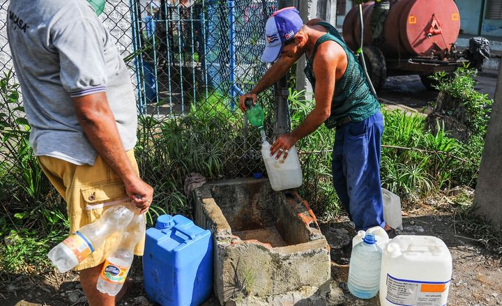 A man fills bottles with water in the Consolacion del Sur neighborhood in the Pinar del Rio province, Cuba on August 19, 2015